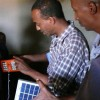 Yoseph Berhane shows a farmer how to use one of his solar lamps.